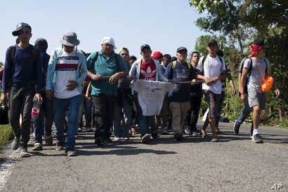 Central American migrants, part of a caravan hoping to reach the U.S. border, walk on a road in Frontera Hidalgo, Mexico, April 12, 2019. The group pushed past police guarding the bridge and joined a group of about 2,000 migrants walking toward Tapac...
