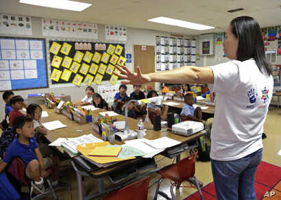 In this Sept. 30, 2016 photo, teacher Regina Yang leads a bilingual Korean-English language immersion classes at Porter Ranch Community School in Los Angeles.