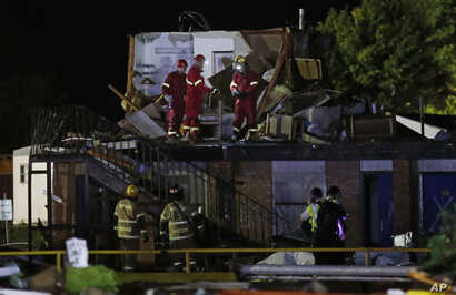 Emergency workers check what is left of the second floor of a hotel, Sunday, May 26, 2019, in El Reno, Ok., following a likely tornado touchdown late Saturday night.