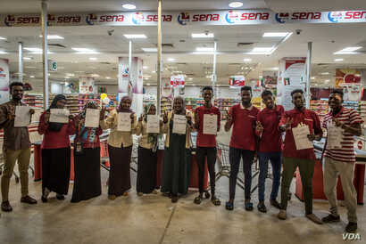 Staff of Sena supermarket hold signs supporting the revolution while refusing to work during a strike, in Khartoum, Sudan, May 28, 2019.