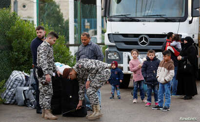 FILE - Lebanese security personnel check luggage of Syrian refugees returning to Syria, in Beirut, Lebanon, Dec. 6, 2018.
