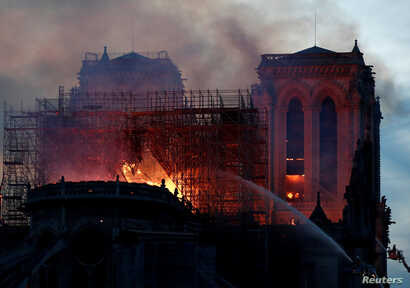 Firefighters douse flames of the burning Notre Dame Cathedral in Paris, France, April 15, 2019.