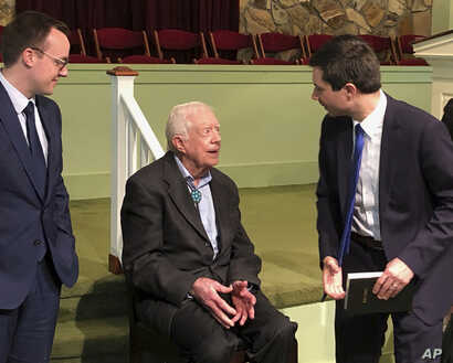 Democratic presidential candidate Pete Buttigieg, right, and his husband, Chasten Glezman, left, speak with former President Jimmy Carter, May 5, 2019 at former President Jimmy Carter's Sunday school class in Plains, Georgia.