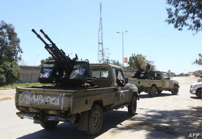 Gun-mounted vehicles belonging to fighters loyal to the internationally recognized Libyan Government of National Accord (GNA) are pictured near a military compound in a suburb of the capital Tripoli on April 9, 2019.