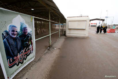 A poster with a picture of a martyr, member of Shiite Popular Mobilization Forces with Iranian Revolutionary Guard Commander Qassem Soleimani is seen at Iraqi side of the Shalamcha Border Crossing, Iraq, Nov. 4, 2018.