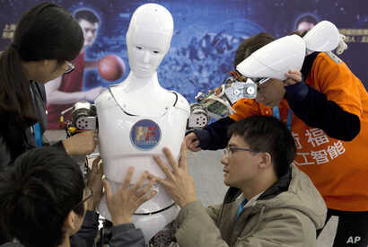 FILE - Chinese students work on the Ares, a humanoid bipedal robot, displayed during the World Robot Conference in Beijing, Oct. 21, 2016.