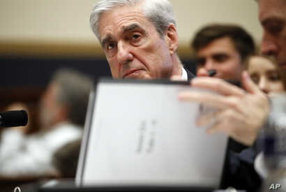 FILE - Former special counsel Robert Mueller checks pages in the report as he testifies before the House Judiciary Committee hearing on his report on Russian election interference, on Capitol Hill, July 24, 2019.