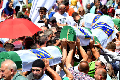 Bosnian Muslims carry caskets of the 33 newly identified bodies of the 1995 Srebrenica massacre before their inhumation at the Potocari Memorial Cemetery near the Eastern-Bosnian town of Srebrenica.
