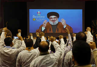 FILE - Hezbollah scouts raise their fists and cheer as they listen to a speech of Hezbollah leader Hassan Nasrallah, via video link, during a rally in southern Beirut, Lebanon, April 22, 2019.