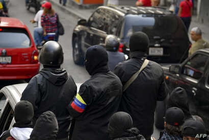 "Masked members of a ""colectivo"" -pro-government cells- attend a rally in Caracas on Jan. 7, 2019."