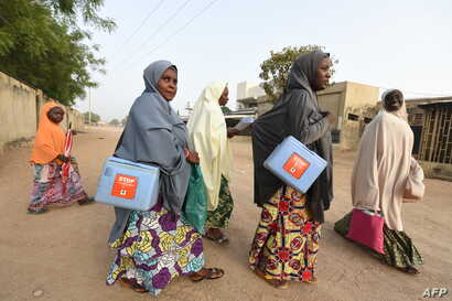Health workers walk from house to house in search of children to immunize during vaccination campaign against polio at Hotoro-Kudu, Nassarawa district of Kano, in northwest Nigeria, April 22, 2017.