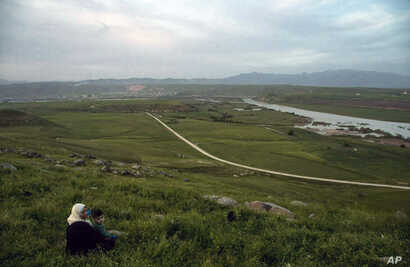 In this file photo dated May 1, 2019, a woman and child sit on a hill overlooking the Euphrates River in Derik, Syria. Turkey wants to establish a safe zone up to 25 miles (40 kilometers) deep, east of the Euphrates River in Syria, that effectively amounts to almost all the territory controlled by Syrian Kurdish fighters.