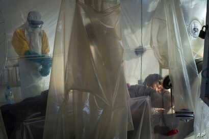 FILE - Health workers wearing protective gear check on a patient isolated in a plastic cube at an Ebola treatment center in Beni, Congo, July 13, 2019.