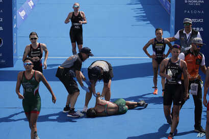 FILE - Mexico's Cecilia Perez, center, collapses after competing in a women's triathlon test event at Odaiba Marine Park, a venue for marathon swimming and triathlon at the Tokyo 2020 Olympics in Tokyo, Aug. 15, 2019.