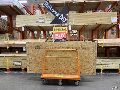 A shopper stands with a dolly of plywood at The Home Depot ahead of Hurricane Dorian on Aug. 29, 2019, in Pembroke Pines, Fla.