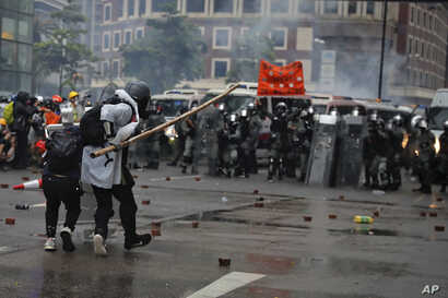 Protesters use bamboo sticks as they face riot police during a protest in Hong Kong, Aug. 25, 2019.