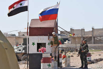 FILE - A Russian soldier places the national flag at the Abu Duhur crossing on the eastern edge of Idlib province, Sept. 25, 2018.