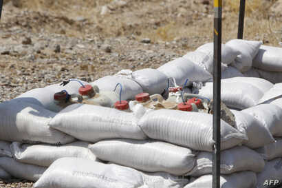 Explosive devices cleared by Iraqi mine clearers working for Halo Trust, a non-profit organization specialized in mine removal, are placed on sand bags in an agricultural and industrial field near the Iraqi town of Baiji, Aug. 25, 2019.
