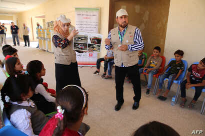 Members of the Iraqi non-profit organization IHSCO hold information sessions with pupils in Iraq's Baiji about mine fields and methods to protect themselves from possible booby-trapped items, Aug. 25, 2019.