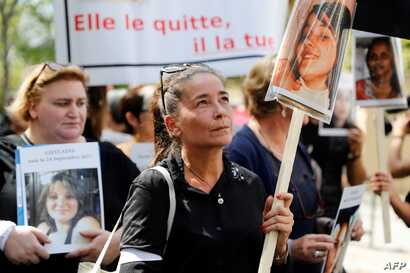 A woman holds a victim's picture as she marches with other women denouncing violence against women, on the opening day of a multiparty debate on domestic violence, in Paris, Sept. 3, 2019.