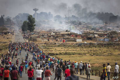 A mob armed with spears, batons and axes run through Johannesburg's Katlehong Township during anti-foreigner violence, Sept. 5, 2019.