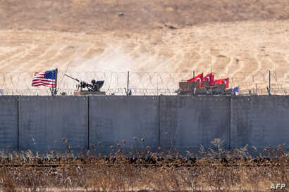 FILE - U.S. and Turkish armored vehicles take part in their first joint patrol with Turkey under a deal reached between Washington and Ankara, at the border with Syria near Akcakale, in the Sanliurfa province of Turkey, Sept. 8, 2019.