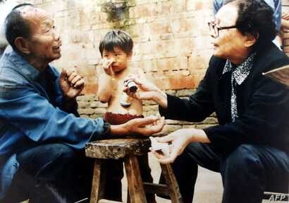 This undated photos shows retired doctor Gao Yaojie, 74, right, applying medicine to a villager's arm as she helps people from neglected AIDS villages in the central China province of Henan. Huge numbers of villagers contracted AIDS or HIV by selling blood for money while local authorities have tried to keep quiet and have refused any help to the villagers.