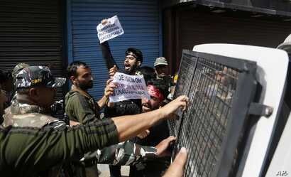 Indian policemen detain Kashmiri Shiite Muslims as they shout pro-freedom slogans after they made an attempt at a religious procession during restrictions in Srinagar, Indian controlled Kashmir, Sept. 8, 2019.