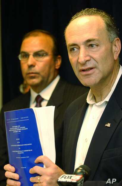 Sen. Charles Schumer, D-N.Y., right, is flanked by John D'Amato, an attorney for the victims of the Sept. 11, 2001, attacks, as he faces reporters in New York, July 27, 2003, with a copy of the government report on the attacks.