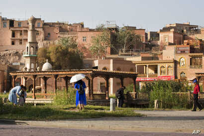 FILE - Visitors walk past the old city district in Kashgar, western China's Xinjiang region, Aug. 31, 2018. Police confirmed that Lu Guang, a prominent Chinese photographer who went missing more than a month ago was arrested, his wife said.