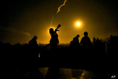 FILE - Syrian Democratic Forces fighters watch illumination rounds light up Baghuz, Syria, as the last pocket of Islamic State militants is attacked, March 12, 2019.