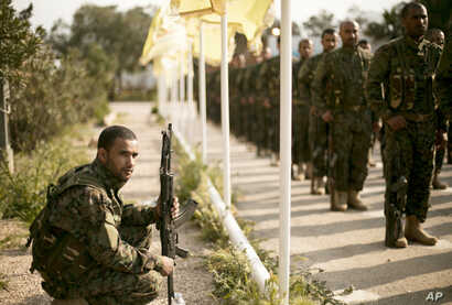 FILE - Syrian Democratic Forces stand in formation at a ceremony to mark their defeat of Islamic State militants in Baghuz, at al-Omar Oil Field base, Syria, March 23, 2019.
