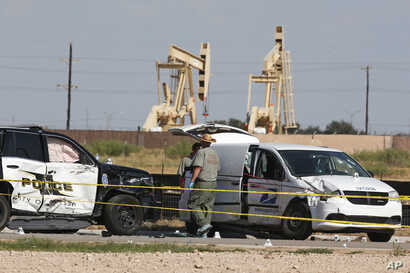 FILE - Law enforcement officials process the crime scene Sept. 1, 2019, in Odessa, Texas, from Saturday's shooting which ended with the alleged shooter being shot dead by police in a stolen mail van, right.