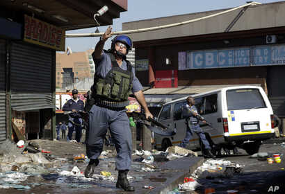 A riot police officer throws a tear gas canister as looters make off with goods from a store in Germiston, east of Johannesburg, South Africa, Sept. 3, 2019.