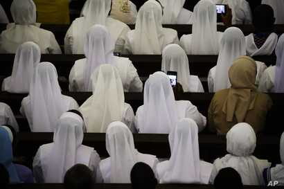 Nuns take photos as Pope Francis presides over a meeting at the Cathedral of the Immaculate Conception, in Maputo, Mozambique, Sept. 5, 2019.