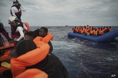 Migrants on a blue rubber boat wait to be rescued some 14 nautical miles from the coast of Libya in Mediterranean Sea, Sept. 8, 2019.