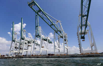 FILE - Large cranes used to unload container ships are shown at Port Miami in Miami, July 24, 2019.