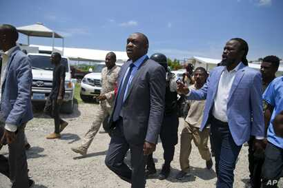 Opposition senators Youri Latortue, center, walks with Antonio Cheramy, right, towards the parliament building before a vote to ratify designate Prime Minister Fritz William Michel, in Port-au-Prince, Haiti, Wednesday, Sept. 11, 2019.