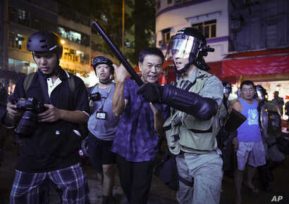 A Pro-China supporter, center, is escorted by police after confronting journalists in north point, Hong Kong, Sept. 15, 2019.