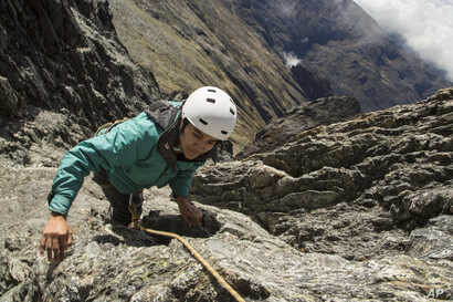 In this May 26, 2019 photo, scientist Cherry Andrea Rojas scales rocks during an expedition to the Humbolt glacier, in Merida, Venezuela.