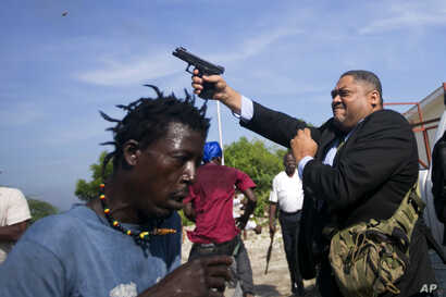 Ruling party Senator Ralph Fethiere fires his gun outside parliament in Port-au-Prince, Haiti, Sept. 23, 2019.