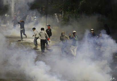Student protesters run from tear gas fired by riot police during a clash in Jakarta, Indonesia, Sept. 30, 2019.