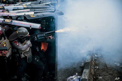 A police officer fires his tear gas launcher during a clash with student protesters in Bandung, West Java, Indonesia, Sept. 30, 2019.