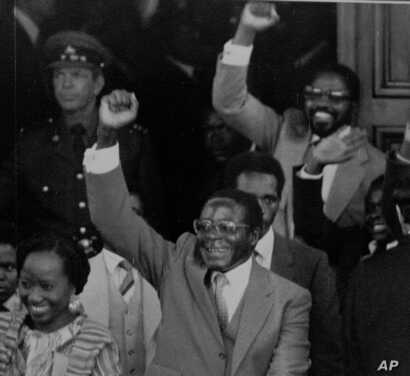 FILE - Zimbabwean Premier Robert Mugabe gives a triumphant salute as he emerges from Parliament following its official opening, May 14, 1980.
