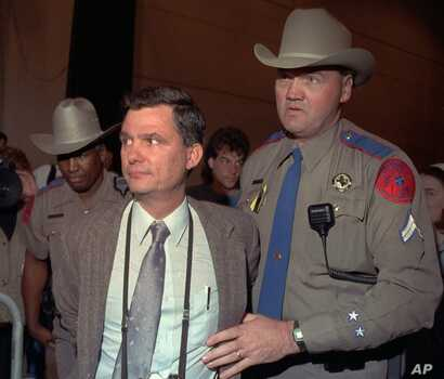 FILE - Texas Department of Public safety officers escort Louis Beam away from a March 18, 1993, Branch Davidian news briefing with the FBI and ATF in Waco, Texas.