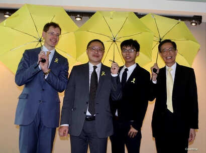 FILE - Joshua Wong, 3rd from left, stands with, from left, Mark Lagon, then-president of Freedom House; Benny Tai, law professor in Hong Kong; and Martin Lee, founder of Hong Kong Democratic Party, at a 2015 event in Washington. (Courtesy of Mark Lagon)
