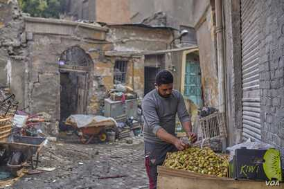"""Ghareb, 34, escaped dire poverty in the countryside to sell fruit in Cairo from an abandoned bakery with six cousins. He says, """"I don't care if Sissi stays or goes. I just want stability and to run my business."""" Sept. 21, 2019. (H. Elrasam/VOA)"""