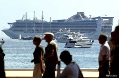 FILE - Pedestrians stroll along the beachfront walkway as a cruise liner and luxury boats are moored in the Bay of Cannes, May 14, 2004.