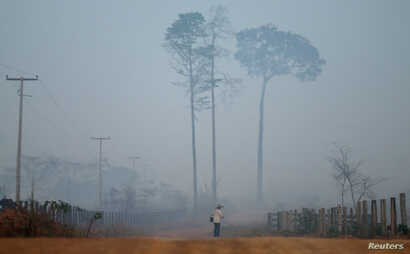 FILE - A man walks amid smoke from a burning tract of Amazon jungle as it is cleared by loggers and farmers near Porto Velho, Brazil, Aug. 28, 2019.
