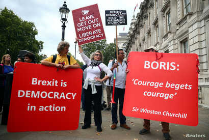 Pro-Brexit and anti-Brexit protesters with placards stand together at Westminster in London, Britain, Sept. 3, 2019.